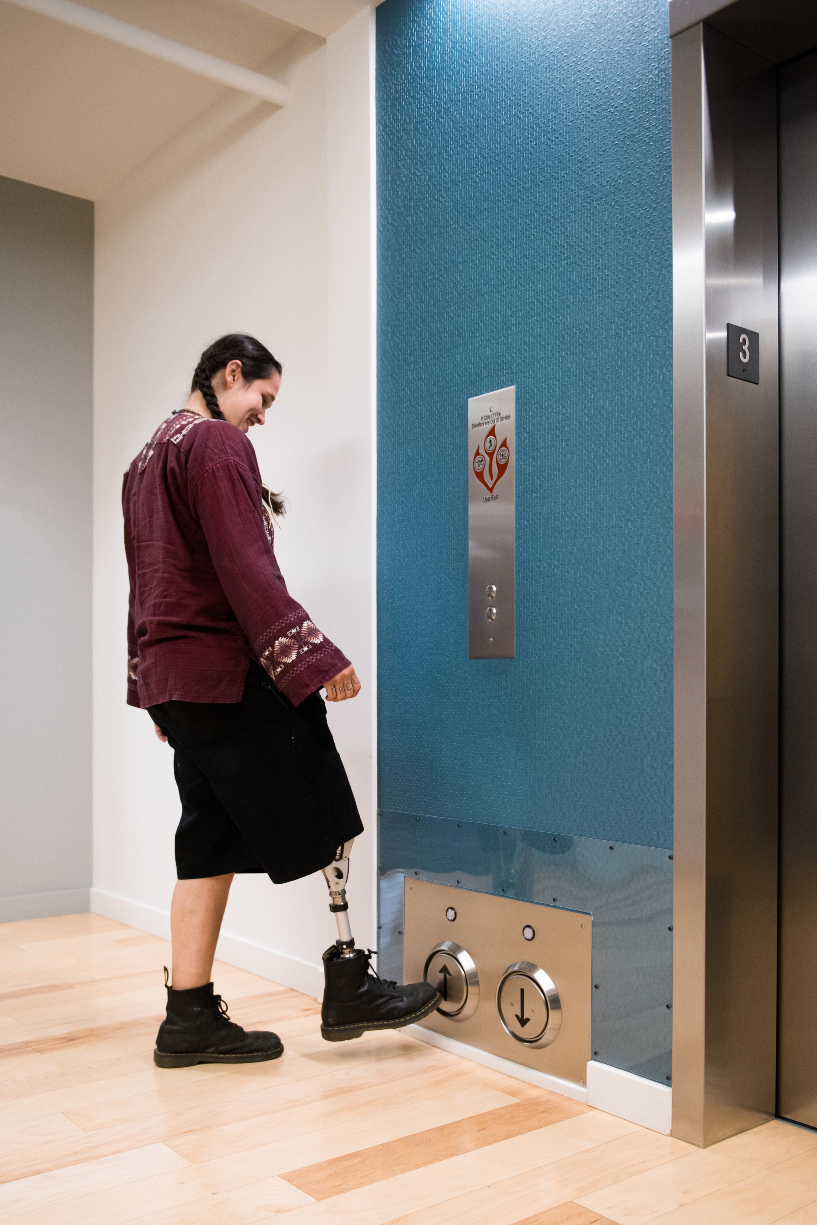 Person pushing UDL Elevator down arrow