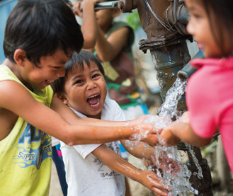 Children enjoying water from a WaterCredit-funded water connection, where an old handpump was upgraded to a mechanical pump, Philippines, 2016.