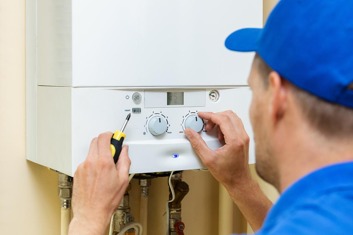 repair man turning central heating dials