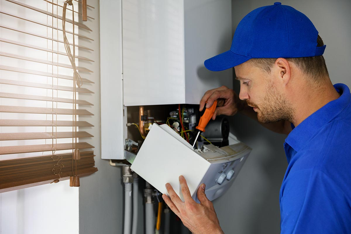 repair man with screwdriver fixing central heating unit