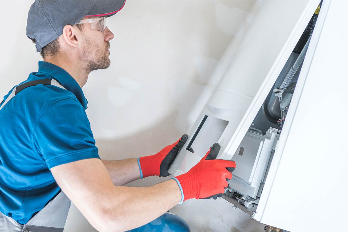 repair man turning central heating dials