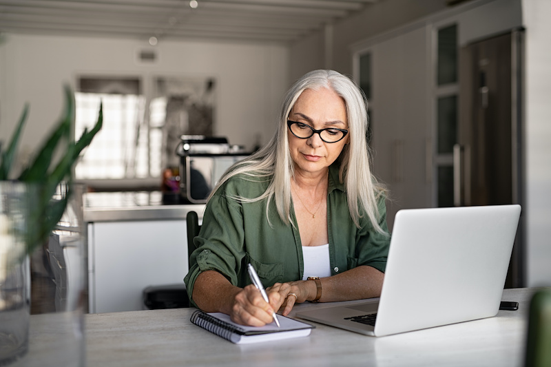 A middle-aged investor woman is sitting at her desk, writing on a piece of paper with her laptop open in front of her.