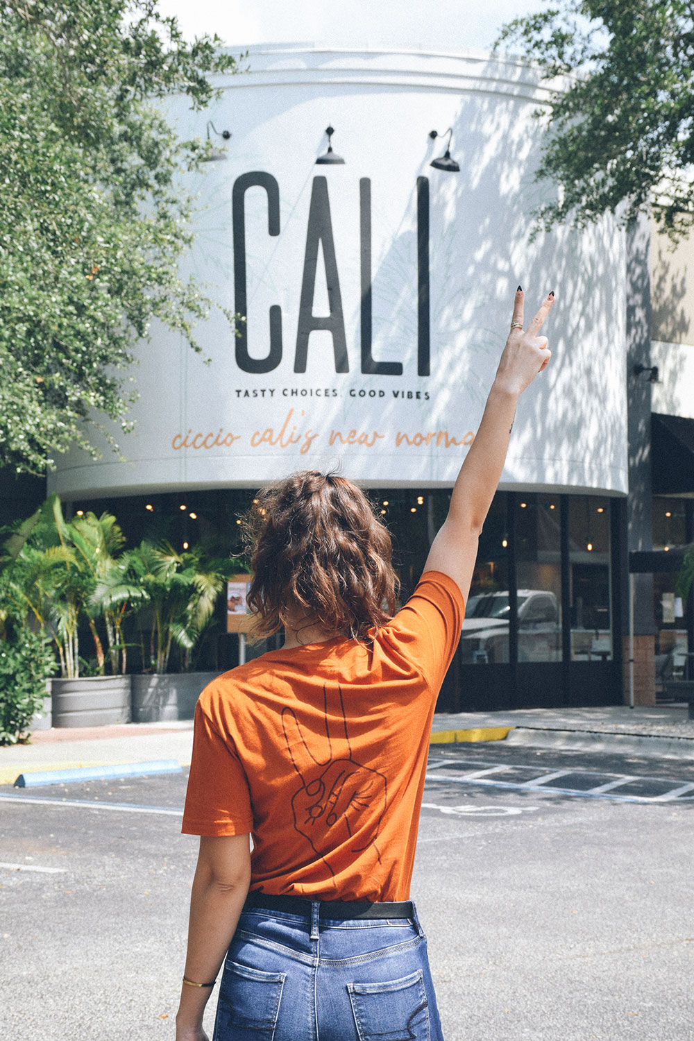 Woman standing in front of a Cali Restaurant giving a peace sign