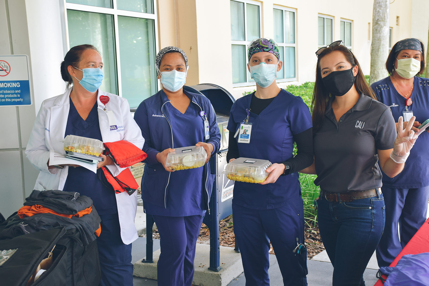 Medical professionals receiving take-out food from Cali