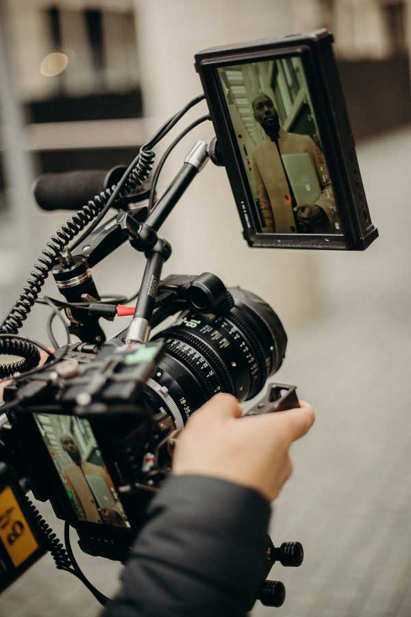 A high end camera with an attached screen and flash being aimed to get the perfect shot for creative content design and content creation