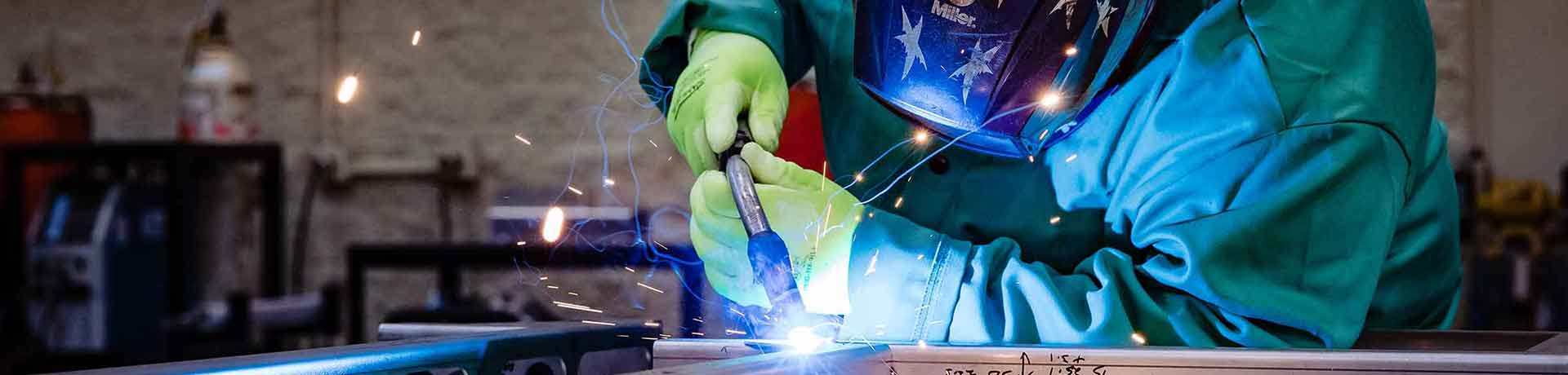 Services Hero Image of Hidaka Welder Welding With Mask On - Dot The i Creative Digital Marketing Services
