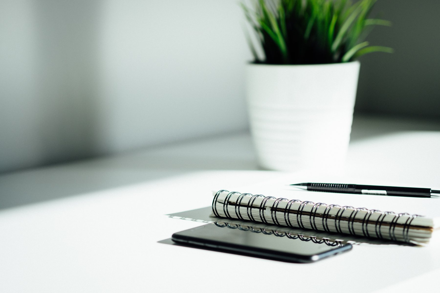 a desk with a plant, pen, notebook and iphone