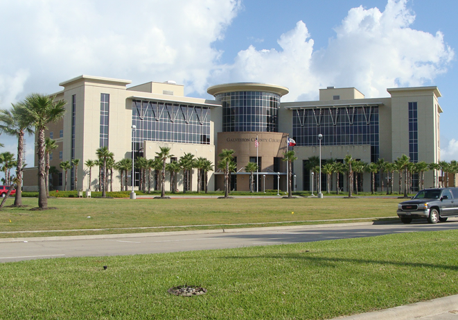A building with palm trees, grass and a street in the front