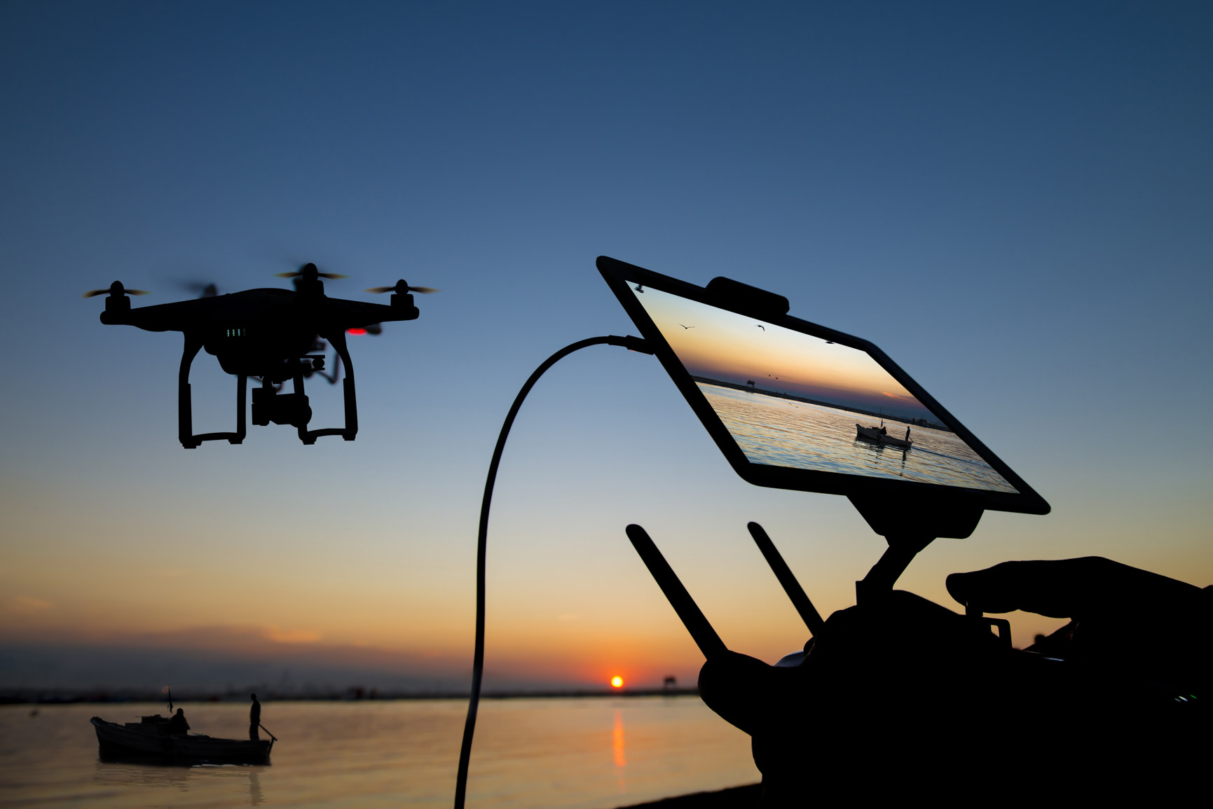 Drone controller with iPad screen attached flying drone in the distance over water at sunset