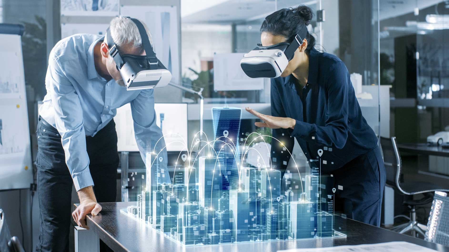 Man and woman of different ethnicities wearing Virtual Reality goggles and collaborating on 3D visualisation of cityscape