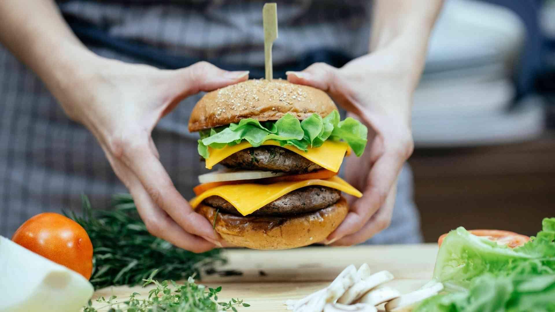 Imagem de uma pessoa preparando hamburger.