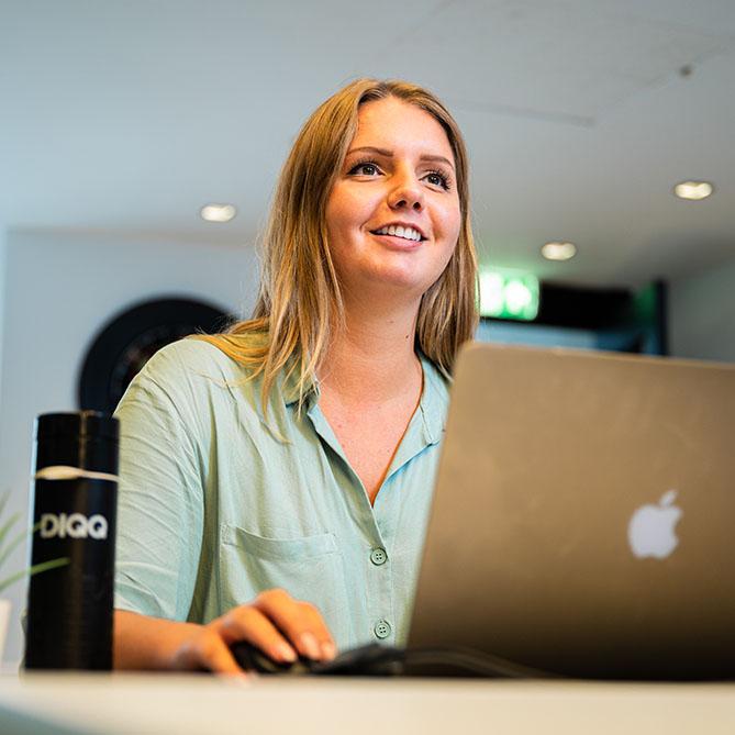 DIQQ medewerker achter haar Apple laptop