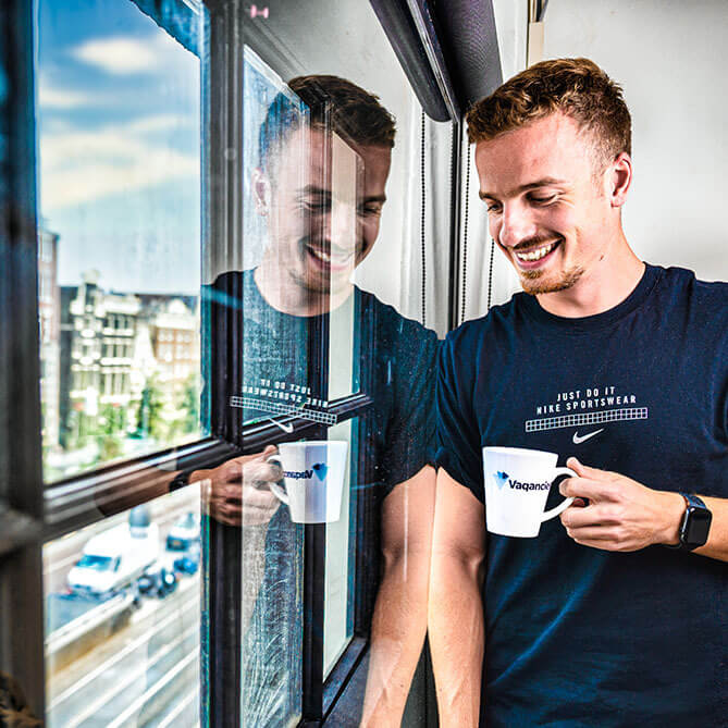 Vaqancies medewerker drinkt koffie en kijkt uit het raam