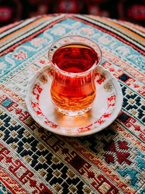 A glass of spicy Iranian chai placed on a Persian rug for a bride before her wedding