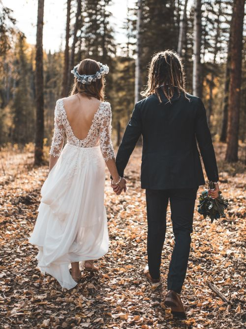 A man and woman who have eloped holding hands as they walk through a forest