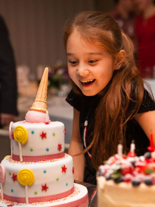 Photograph of a happy young girl blowing out candles on a cake at a kid's party