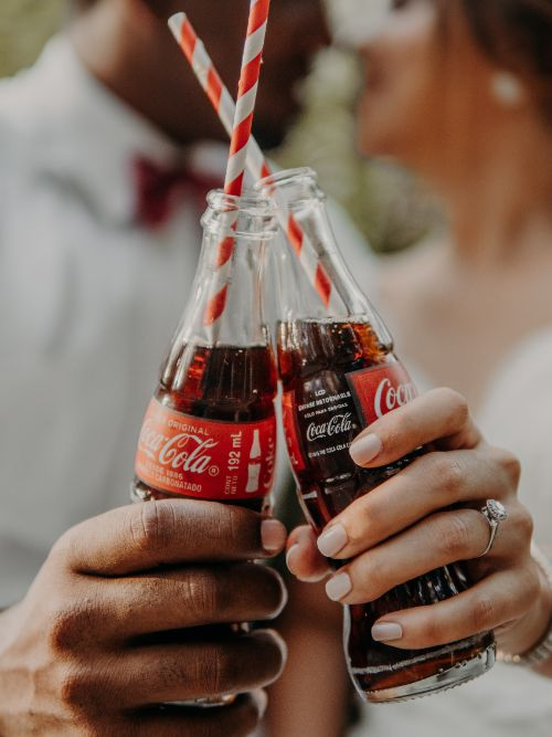 A photograph of two people holding branded Coca-Cola bottles up to the camera