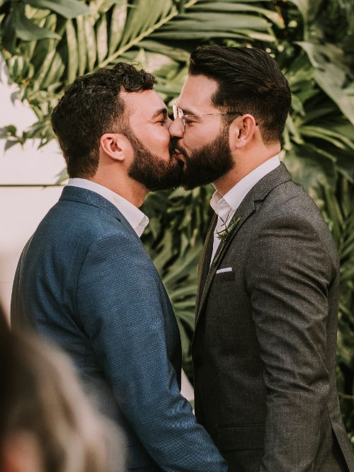 Same sex couple kissing each other on their wedding day with other LGBTQ guests