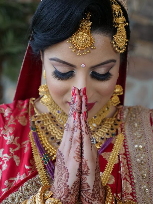 A Sikh bride wearing a red and gold dress praying before her Anand Karaj wedding ceremony