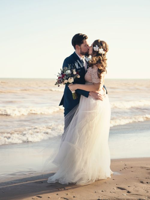 A well-dressed couple standing on a beach kissing in a cinematic wedding video shoot