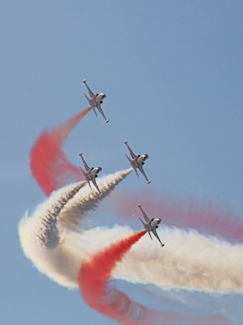 Long lens photo of a formation of planes with red and white smoke at a live airshow event