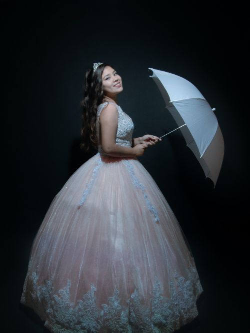Photograph of a young school student wearing a prom dress with a white umbrella
