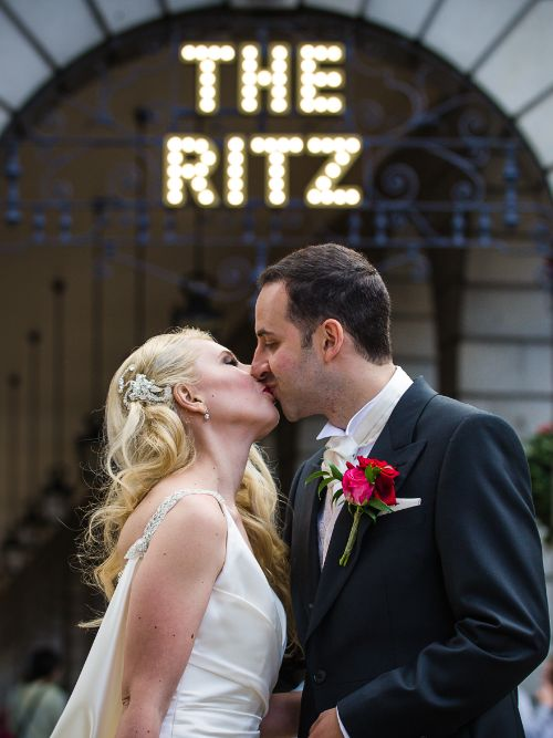 A Jewish couple posing for a wedding photograph outside The Ritz Hotel in London