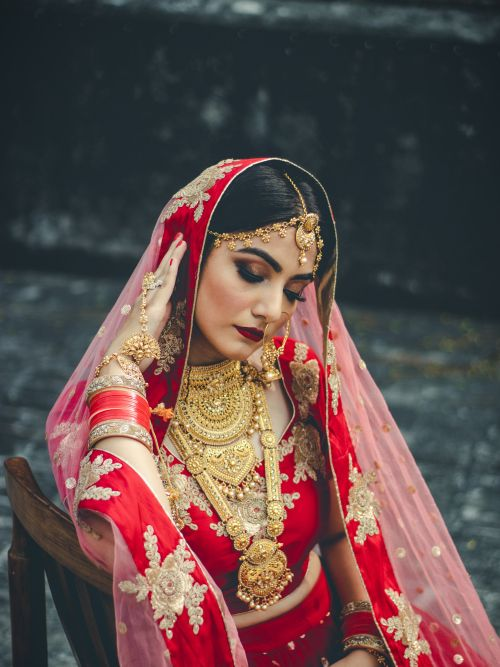 A Sikh bride sat in a chair posing for a photograph wearing a tradition Punjabi wedding dress