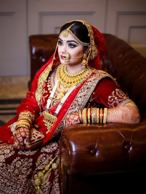 Beautiful Asian bride wearing a red and gold dress with ornate jewellery posing for a photo