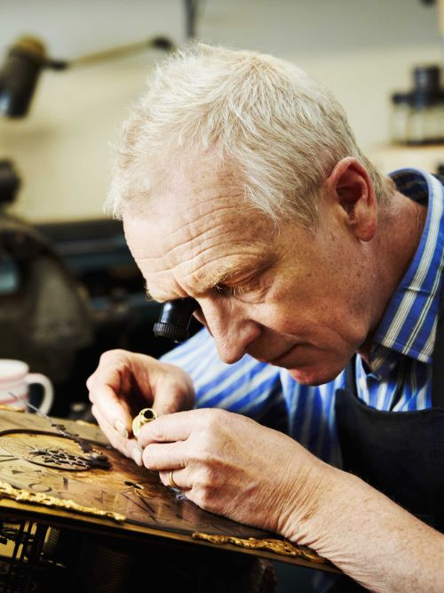 Documentary image of an experienced craftsman working on an antique clock