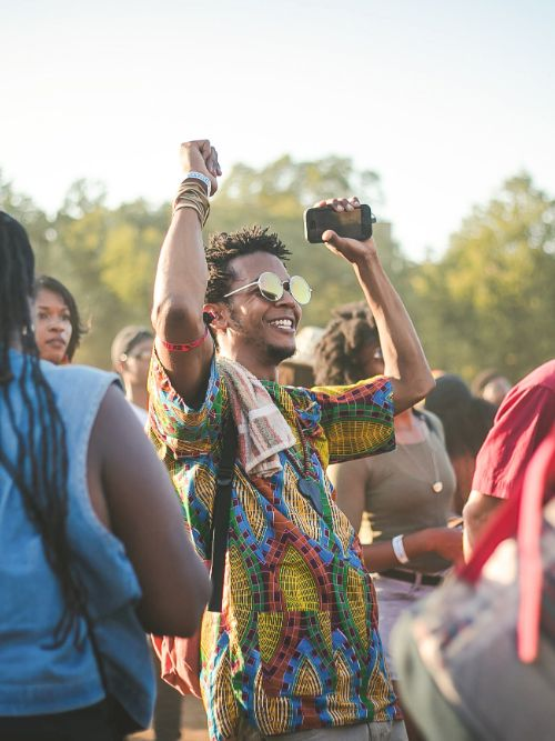 Photograph of a jubilant young man wearing glasses at a festival dancing and enjoying himself