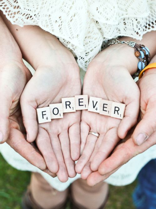 Photograph of a newly engaged couple holding hands with a sign saying 'forever'