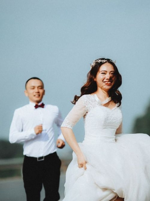 Happy looking Chinese couple be filmed outside in the sunlight on their wedding day