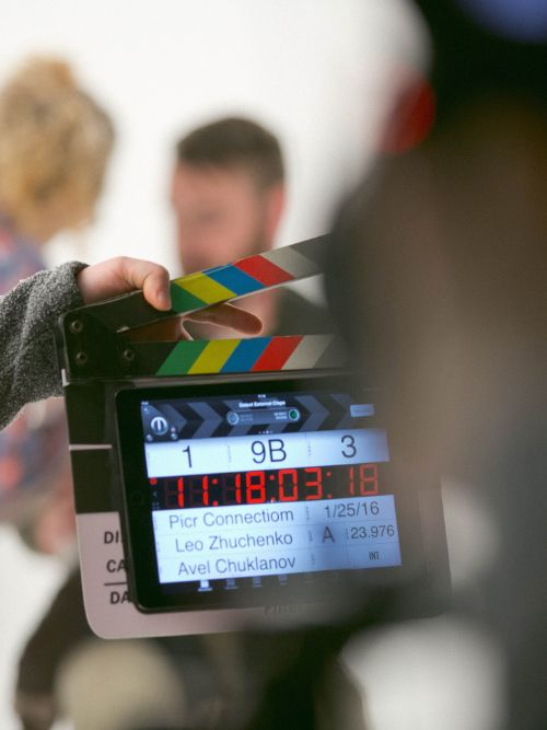 A clapper board held up in front of a scene being filmed by a freelance filmmaker