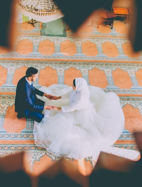 Arabic couple in a mosque holding hands during filming on their wedding day