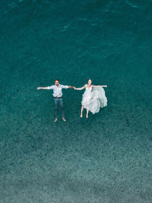 Aerial view of a bride and groom floating in the sea wearing their wedding outfits