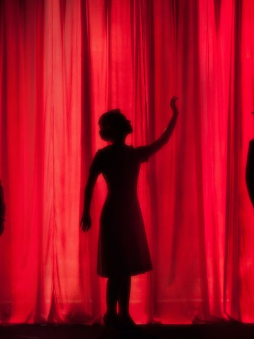 Silhouette image of an actress on stage with a red curtain in the background behind