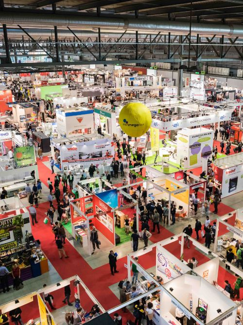 Overhead shot of a busy exhibition hall with lots of people walking around trade stands