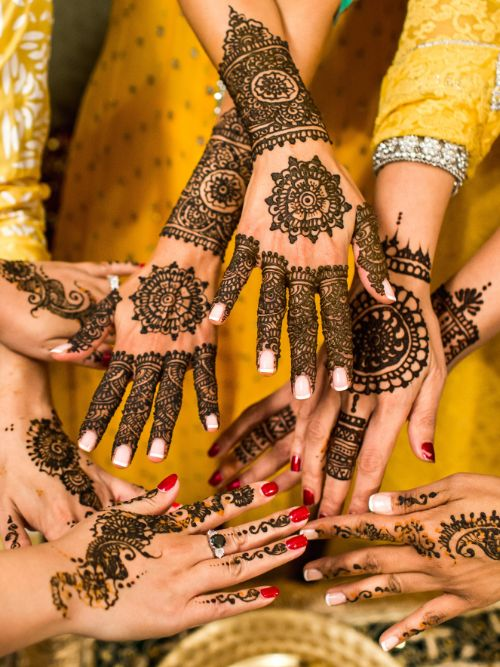 Indian bride and her bridesmaids showing their Henna tattoos to photographer during a Hindu wedding ceremony