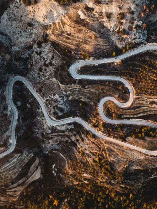 Aerial filming of a car on twisty mountain road shot with a DJI Inspire drone