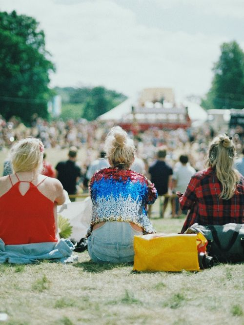 A view of a festival stage shot over the shoulder of three people sat on the ground