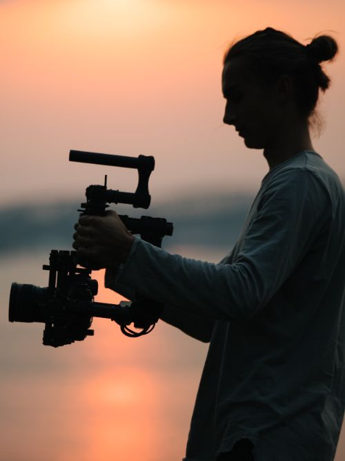 A freelance videographer holding a DSLR video camera on a gimbal with the sunset in the background