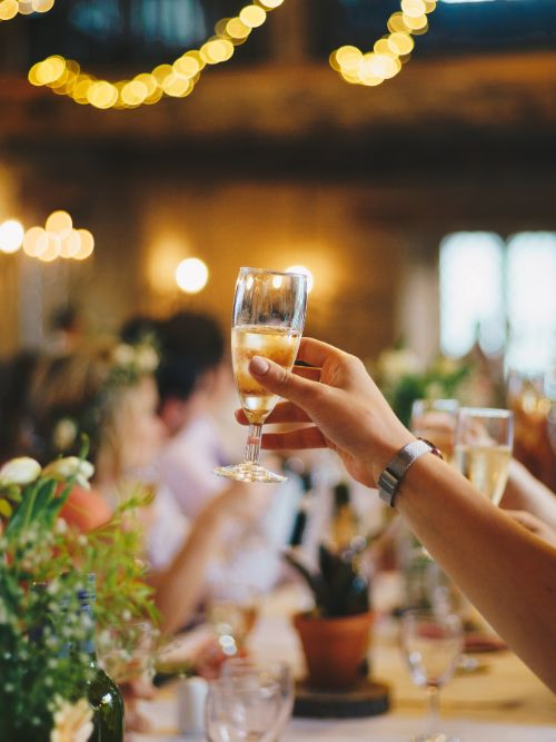 People sat at a table enjoying an event with a person holding up a champagne glass to the video camera