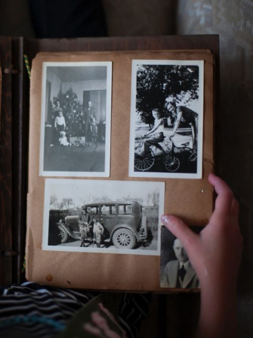 Old black and white photographs in an album showing a couple with their family