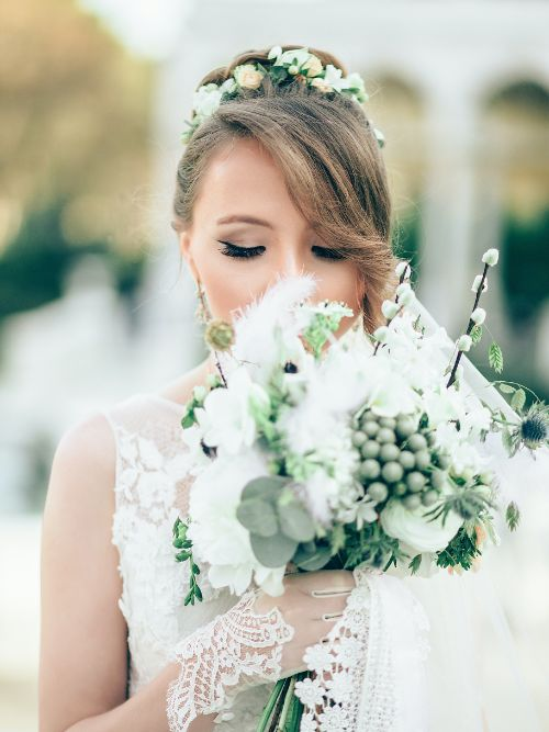 A bride in a white dress being filmed smelling her flowers before her wedding ceremony