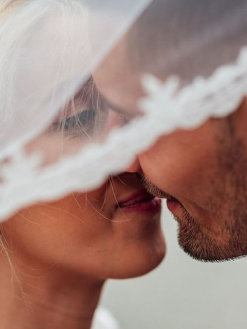 A Greek looking couple kissing underneath lace veil in a pose for their wedding photographer