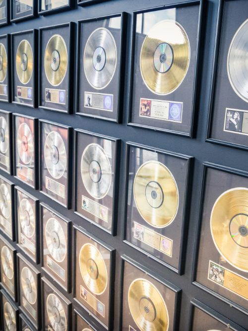 A collection of music awards comprising silver gold and platinum discs