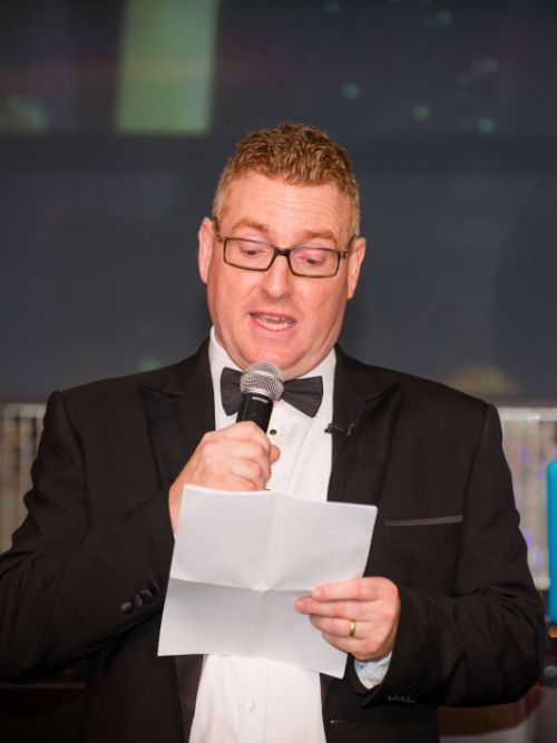 Man wearing a black-tie dinner suit stood by a microphone announcing winners at an awards event