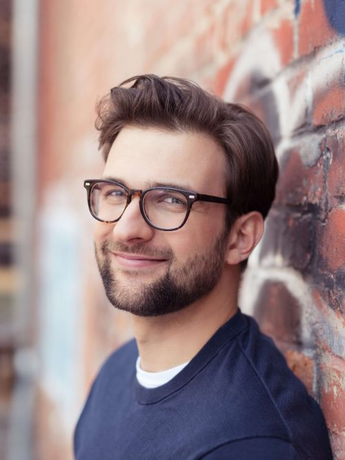 A head and shoulders shot of a man in glasses leaning again a wall having his picture taken