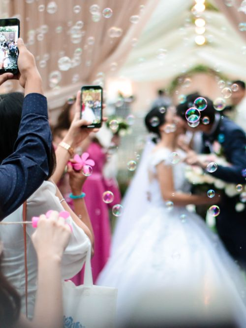 Editing of a wedding couple outside a church kissing with bubbles in the foreground